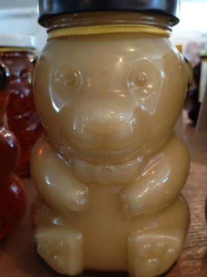 Raw creamed honey in a glass bear jar
