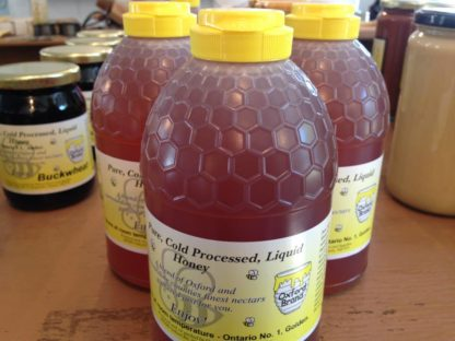 Squeeze bottles of pure, cold pressed liquid honey with buckwheat honey in the background